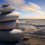 Photograph of a stack of balanced rocks by the beach.