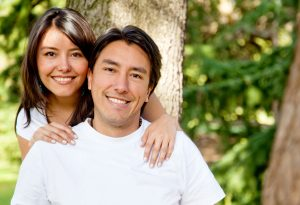 Portrait of man and woman smiling outdoors