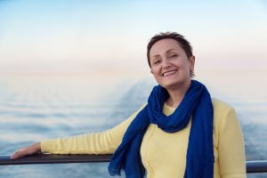Portrait of happy woman relaxing on a luxury cruise liner boat. Beautiful sunset or sunrise blurred background.