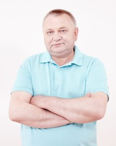 Portrait of aged man wearing blue polo shirt standing with crossed arms white wall – retirement concept