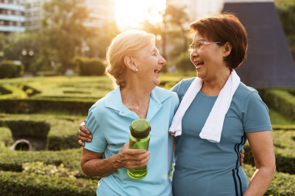 Two women laughing outside. One woman is holding a water bottle, the other has a towel around her neck