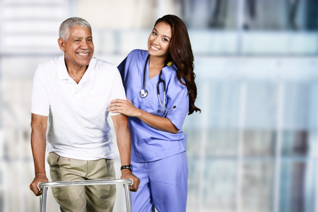Young woman nurse in blue scrubs walking with an older patient using a walker
